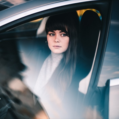 Dark hair girl sitting in car